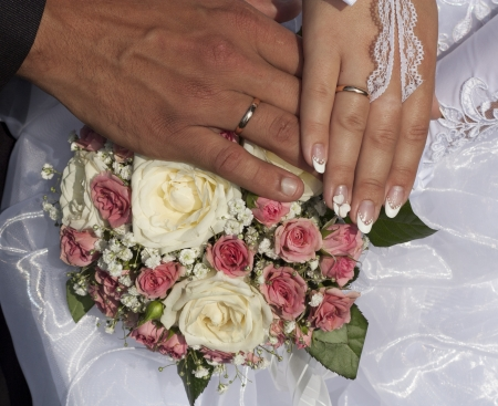Hands of man and woman as bride and groom with wedding rings upon flower. Happy love couples photo. photo
