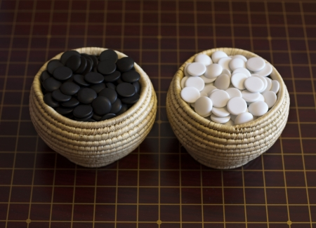 life and death: Goe boardgame  Bamboo baskets with stones for game go on wood  Strategy playing  Logical style photo  Stock Photo