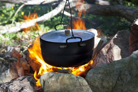 pot on the fire, tourists kettle on hot campfire. Camping photo. photo
