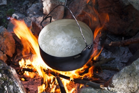 Pot water on the fire, tourists kettle on hot campfire  Camping photo
