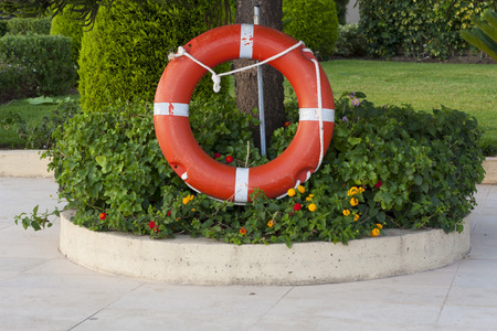 Safe support aid circle with rope  Rescue water red life buoy on flower background  Helpful object photo  photo