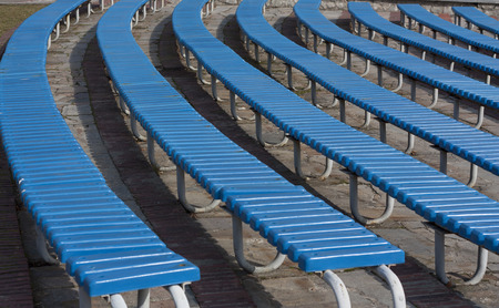 arranging chairs: Row of blue wooden seats on a spectator grandstand photo. Bench in the park for the show Stock Photo