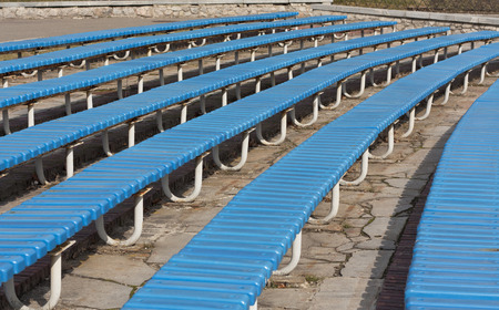 spectator: Row of blue wooden seats on a spectator grandstand photo. Bench in the park for the show Stock Photo