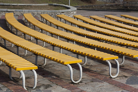 spectator: Row of yellow wooden seats on a spectator grandstand photo. Bench in the park for the show