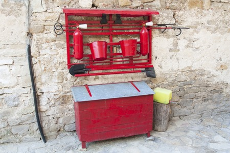 gaff: fire against retro old red axe, shovel, buckets. Fire fighting equipment photo