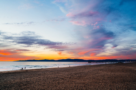 Looking north at the Hermosa Beach Pier, Pacific Palisades and Malibu after sunset with the orange glow in the clouds.