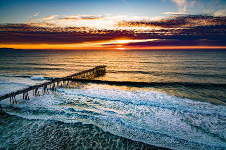 hermosa beach: Aerial view of the sun setting over the Hermosa Beach Pier, and the waves of the Pacific Ocean.