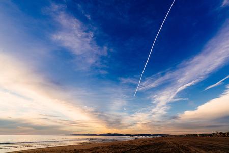 hermosa beach: Clouds and an airplane vapor trail converge at the horizon, in Hermosa Beach, California