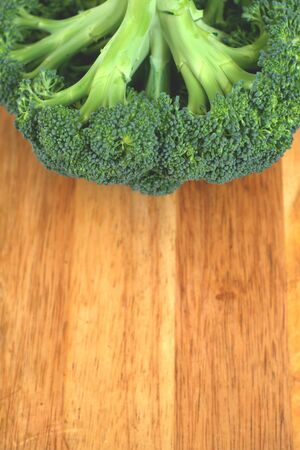 Close up of a plant of broccoli with a wooden chopping board on the background.