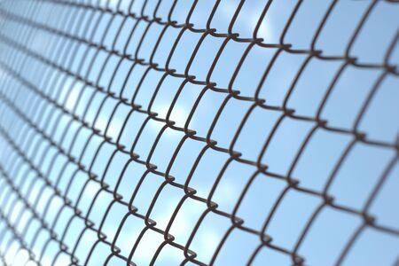 Close up of a wire fence against a clear blue sky, as a concept for imprisonment, jail, sentence, etc. Stock Photo