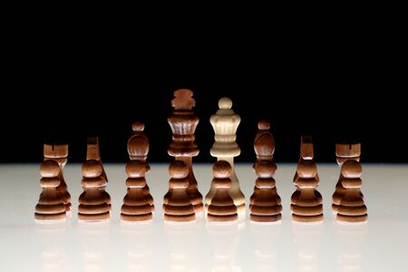 Black chess formation with a single white piece as a concept for undercover operations, infiltration, racial tension, ethnic minorities.