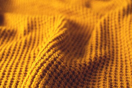 Mustard colored woollen textile. Texture detail close up.