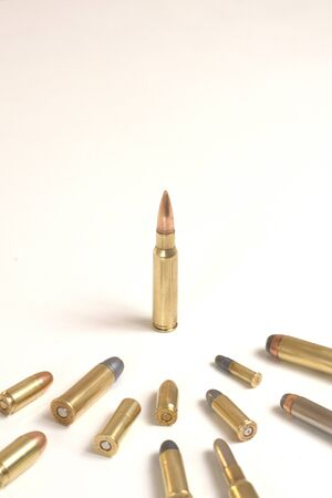 Large bullet standing in front of smaller bullets. Concept for power, obedience, domination, dictatorship.The central bullet is a 7.62 x 51mm NATO.