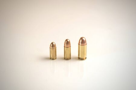 Three bullets of different calibers on a white surface. From left to right:.380 Auto FMJ9x19mm FMJ.45 Auto FMJ Stock fotó
