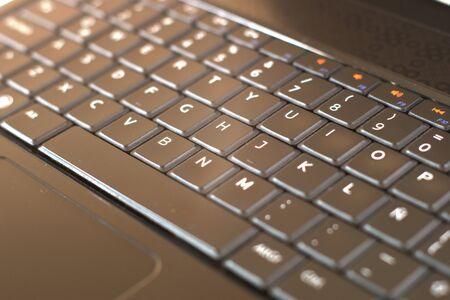 Zwarte laptop computertoetsenbord close-up. Mobiel, draagbaar apparatenconcept. Witte achtergrond. Stockfoto