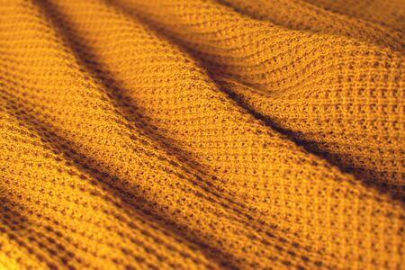 Textile en laine couleur moutarde. Détail de la texture se bouchent.