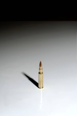 Large bullet (7.62 x 51 mm NATO) on a white surface with dark background. Plenty of negative space.