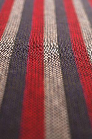 Drap de laine rayé rouge, gris et blanc. Détail de la texture se bouchent. Motif de lignes droites.