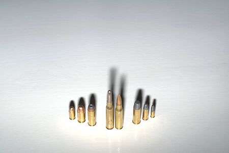 Crime family concept. Bullets standing on a white surface with dark, dramatic shadows. Stock fotó