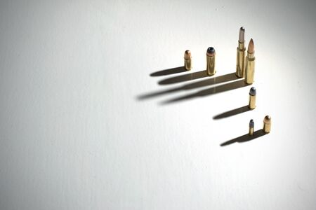 Crime family concept. Bullets on white surface with long, dark shadows. Stock fotó