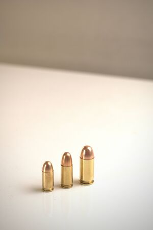 Three bullets of different calibers on a white surface. From left to right: .380 Auto FMJ9x19mm FMJ.45 Auto FMJ
