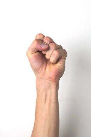 Fist held up high. Symbol of resistance, uprising or protest. White ethnicity.