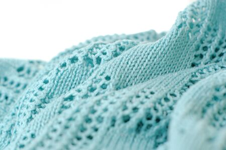 Aquamarine color crochet sweater on white background. Texture detail close up.
