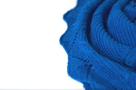 Azure blue crochet sweater on white background. Texture detail close up.