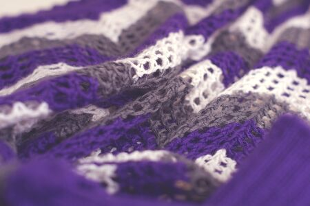 Purple and white striped pattern yarn crochet sweater. Texture detail close up.