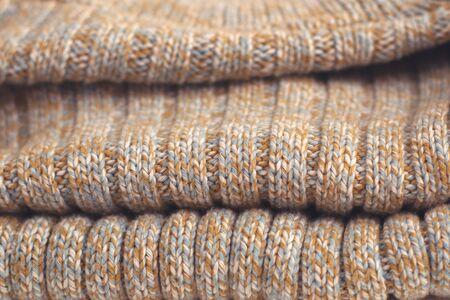 Mottled beige knitted woollen sweater. Texture detail close up.