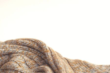 Mottled beige knitted woollen sweater on white background. Texture detail close up. Negative space. Stockfoto
