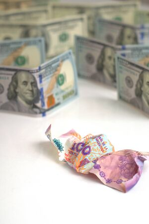 Argentina economic crisis and currency devaluation. Crumpled argentinian banknote and intact US banknotes. Concept metaphor. Reklamní fotografie