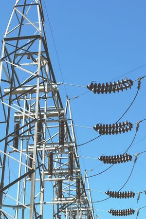 High voltage electrical insulators at a power station. Low angle shot against a blue sky.