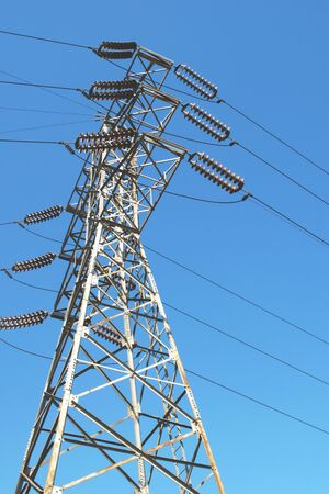 Steel frame electrical pylon. Low angle shot against a blue sky.