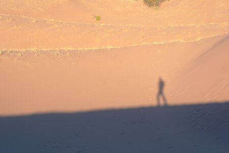 Lone explorer on the desert, casting shadow on the sand dunes on a hot sunny day. Stock fotó