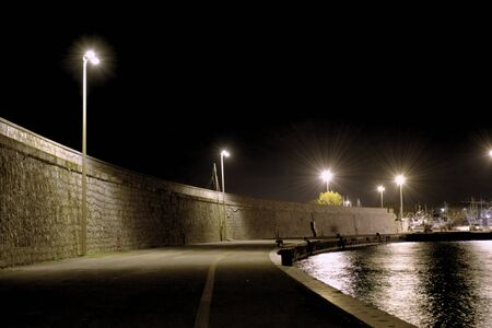 Dark pier sidewalks at night in the city of Terracina, Italy Stock fotó