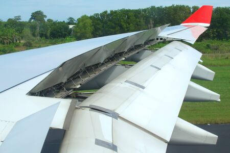 Jet plane air brakes and flaps fully extended after landing. Hydraulic actuators can be seen in the interior of the wing.