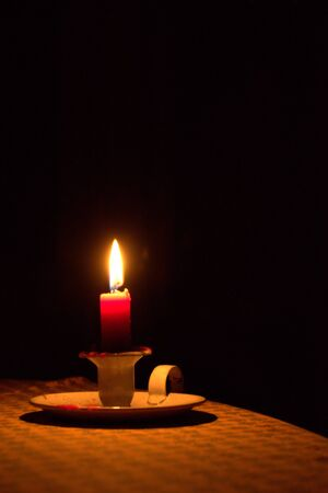 Candle light on a table, shining in the dark. Power outage, blackout concept background.