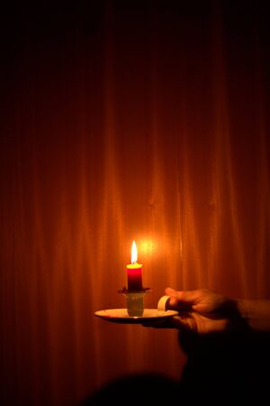 Candle light shining in the dark against wood background. Power outage, blackout concept.