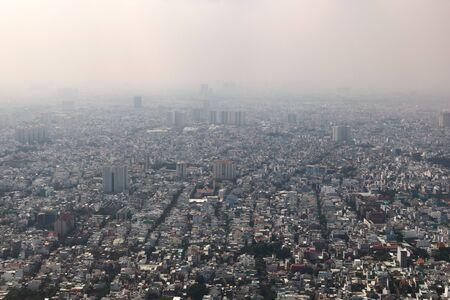 Dense air pollution and smog over Saigon, Vietnam (Ho chi Minh City). Overpopulated city, urban sprawl. Aerial view.