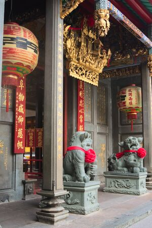 Chinese Imperial guardian lions, made of stone, guarding the gate at a buddhist temple in Saigon, Vietnam (Ho Chi Minh City)