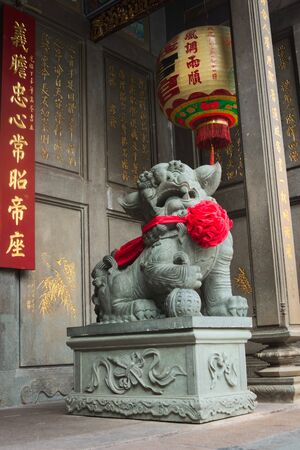 Chinese Imperial guardian lion, made of stone, guarding the gate at a buddhist temple in Saigon, Vietnam (Ho Chi Minh City)