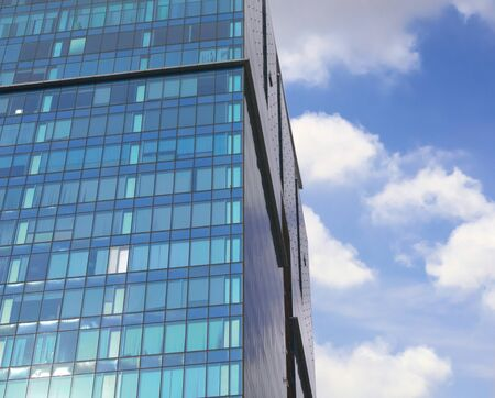 Modern office building exterior. Blue glass facade and blue sky with sparse clouds.