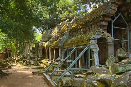 Eastern outer gallery of Ta Prohm temple, in Angkor Wat complex near Siem Reap, Cambodia. Modern restoration scaffolding is seen on the foreground, holding the columns.