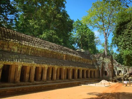 Inner gallery and courtyard of Ta Prohm temple ruins, located in the Angkor Wat complex near Siem Reap, Cambodia. Archeological and restoration scaffoldings can be seen on the background. Archivio Fotografico