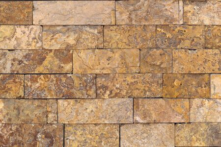 Rust-colored sandstone wall. Natural, rustic style construction.