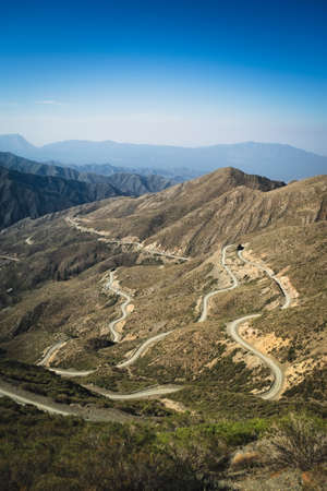 Narrow twisting dirt road across the Andes Mountains in Mendoza, Argentina. Foto de archivo