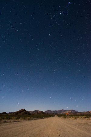 Starry night sky above a dirt road across the desert near Uspallata, Mendoza, Argentina.