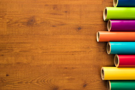 Colored vinyl rolls over wooden background Stock Photo