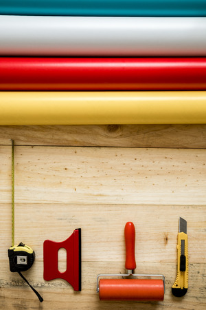 Colorful vinyl rolls on wooden background with your necessary instruments